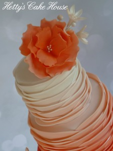 Coral ombre ruffles wedding cake close up
